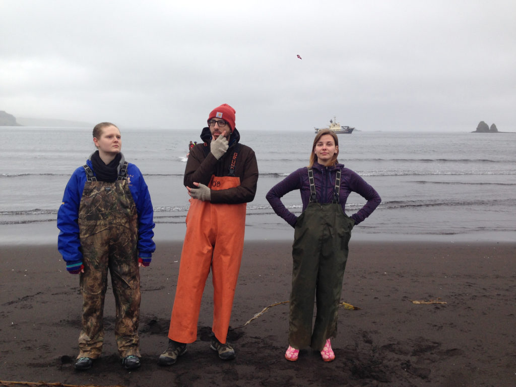 WAYK's 2016 interns, Erin McGarvey, Samuel Catanach, and Robyn Giffen on the beach at Nazan Bay in Atka, Alaska, preparing to board the Tiĝlax̂.